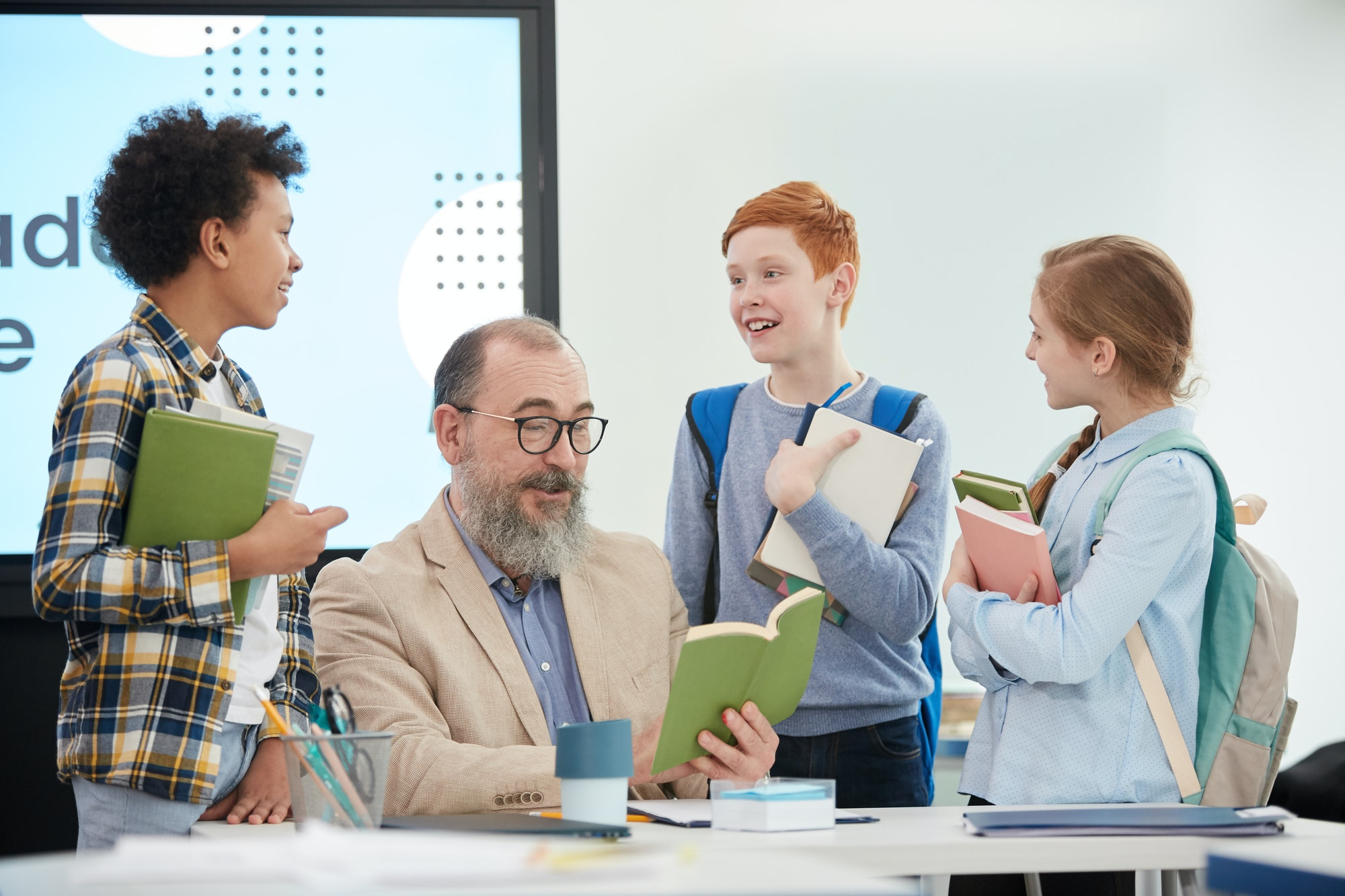 Children Talking to Teacher in School