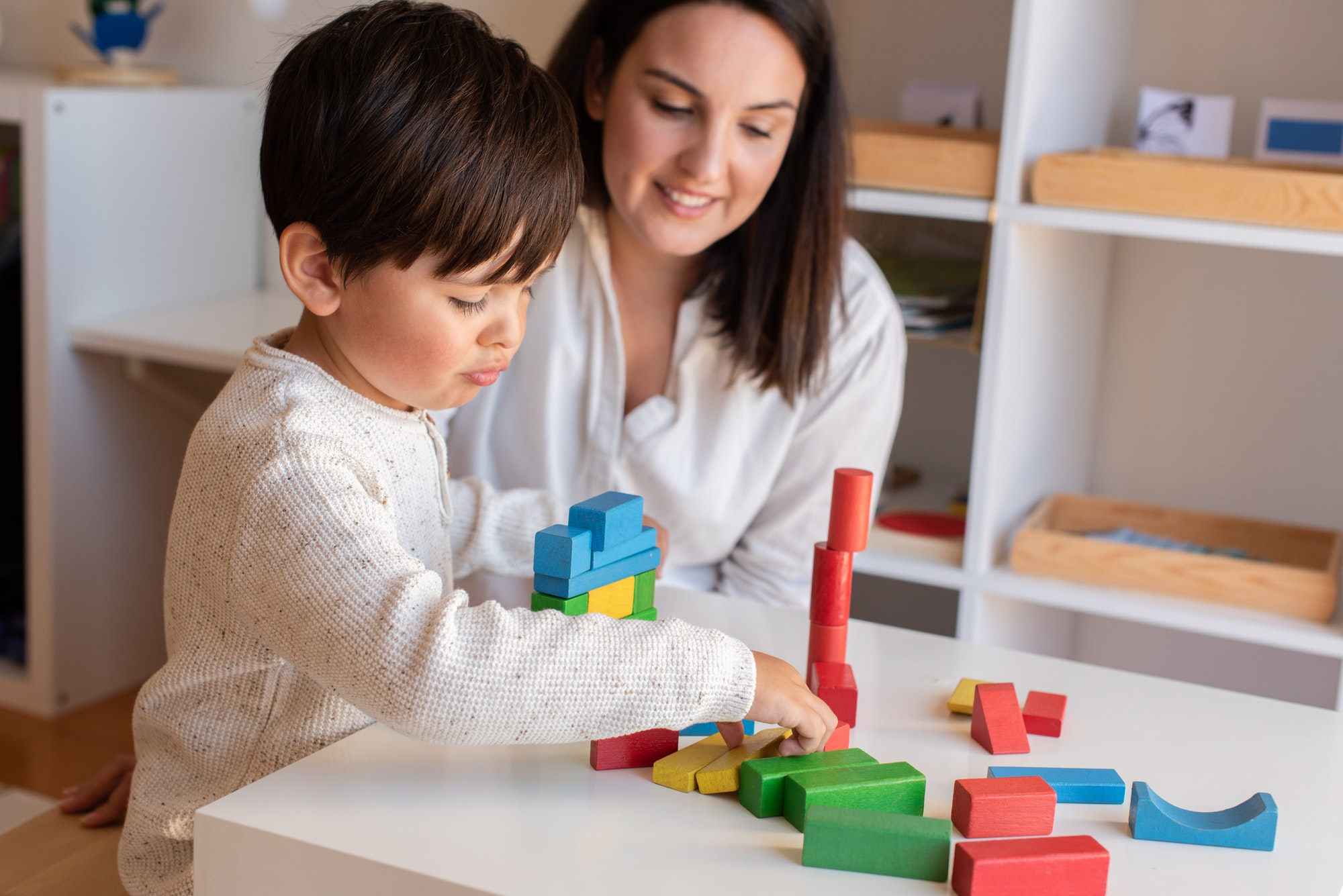 Kid playing with wood blocks and teacher educador help.